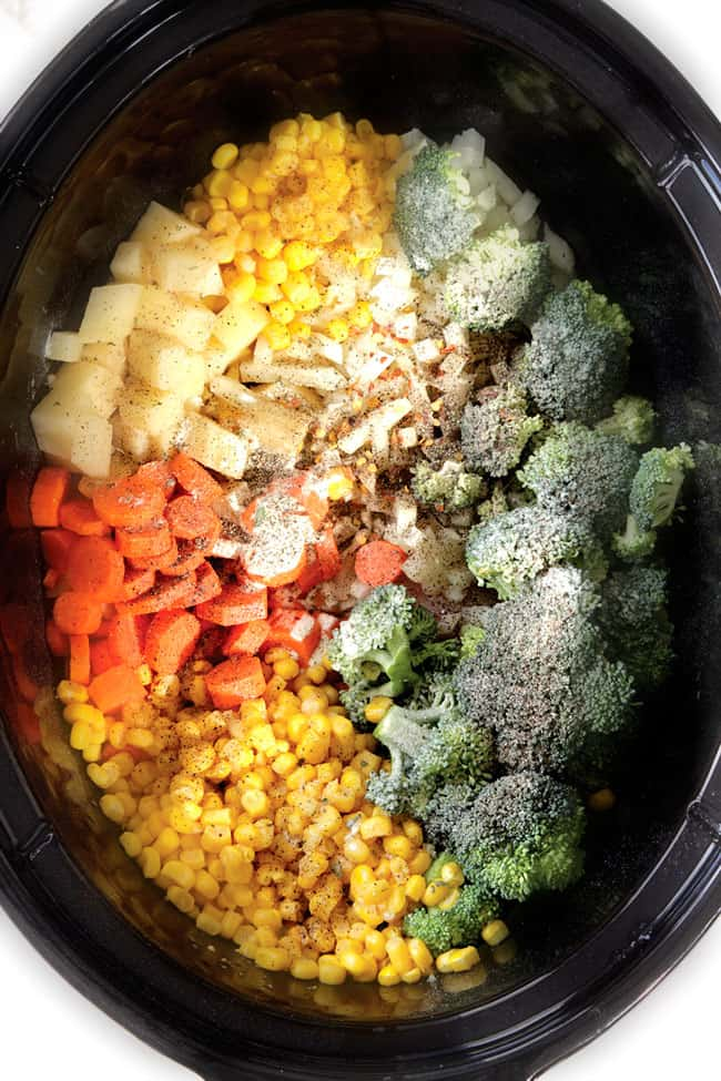 showing how to make chicken corn chowder in the slow cooker by adding chicken, corn, carrots, potatoes, onions, broccoli to crockpot