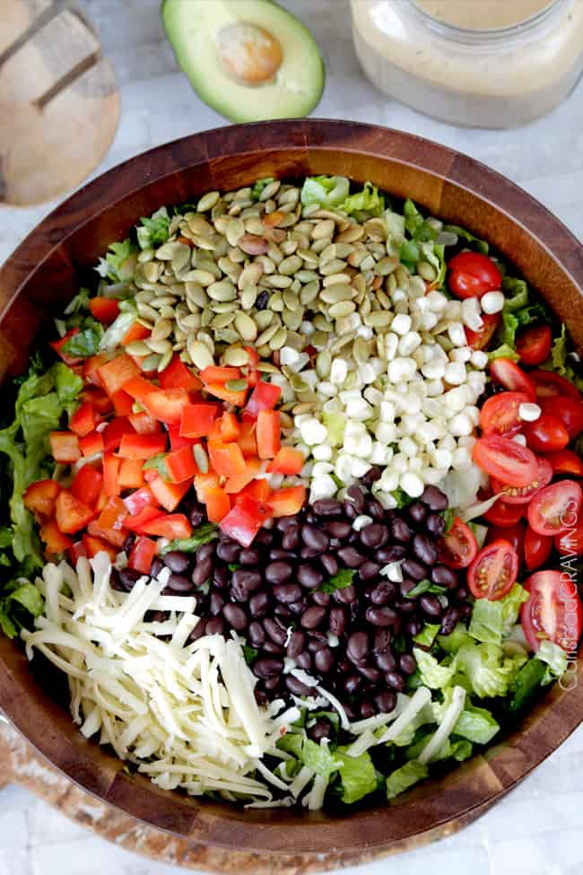 showing how to make healthy Southwest Salad by adding romaine lettuce, tomatoes, black beans, cheese, bell peppers and pepitas
