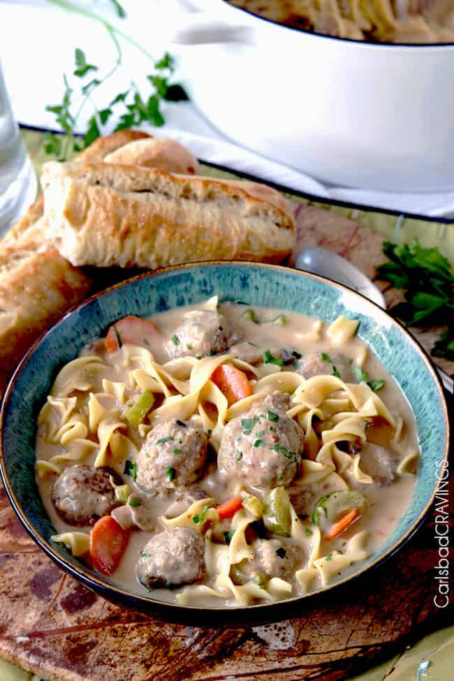 side view of a bowl of meatball soup with juicy meatballs, pasta, carrots, celery, mushrooms