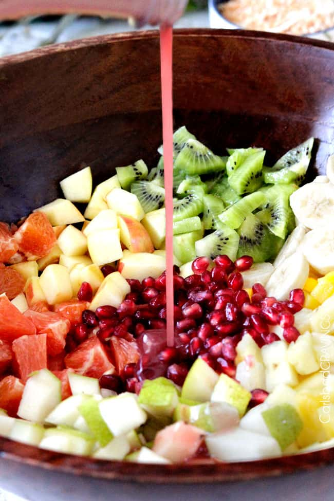 showing how to make tropical fruit salad by adding pomegranate dressing