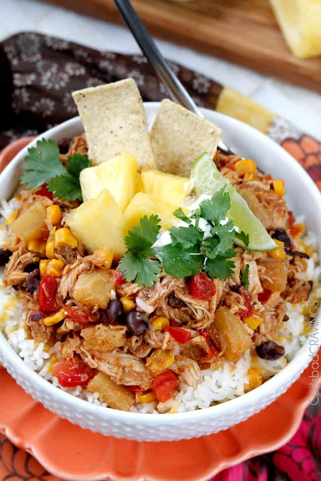 Top view of Pineapple Salsa Chicken in a white bowl garnished with pineapple and chips.