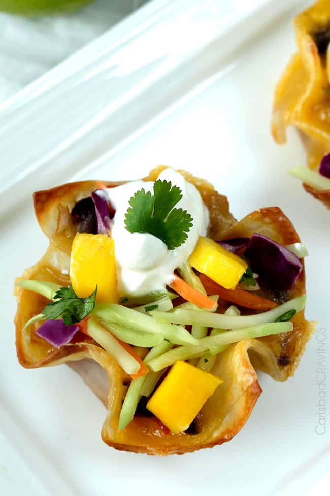 Top view of a Tuna Melt Cups garnished with mango, and herbs.