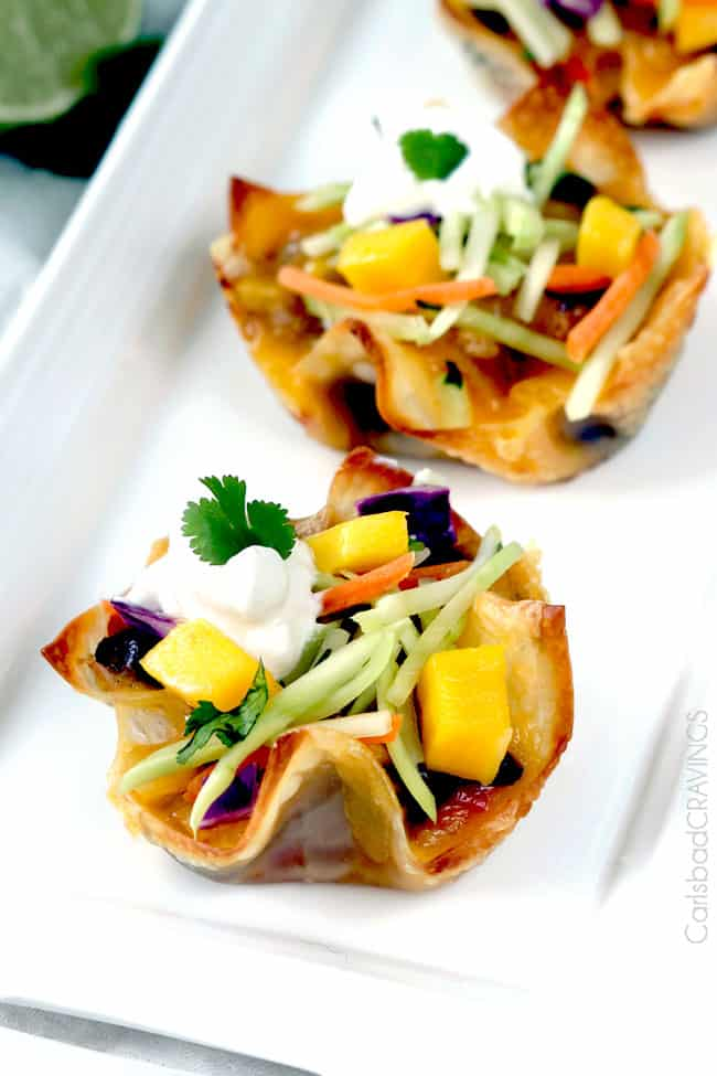 Tuna Melt Cups garnished with mango, and herbs on a white plate.