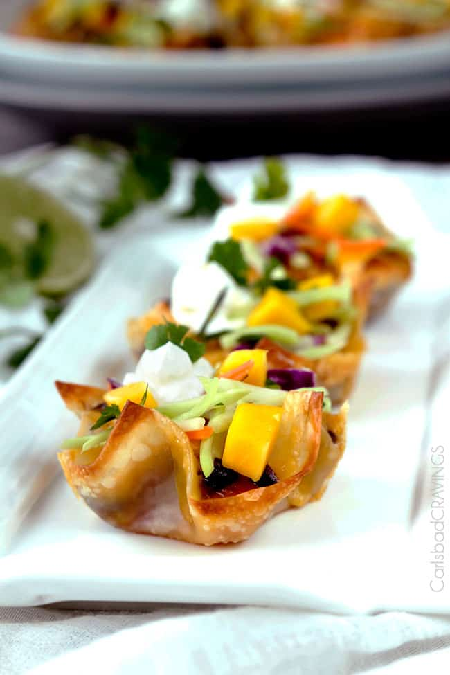Close up of Tuna Melt Cups garnished with mango, and herbs on a white plate.
