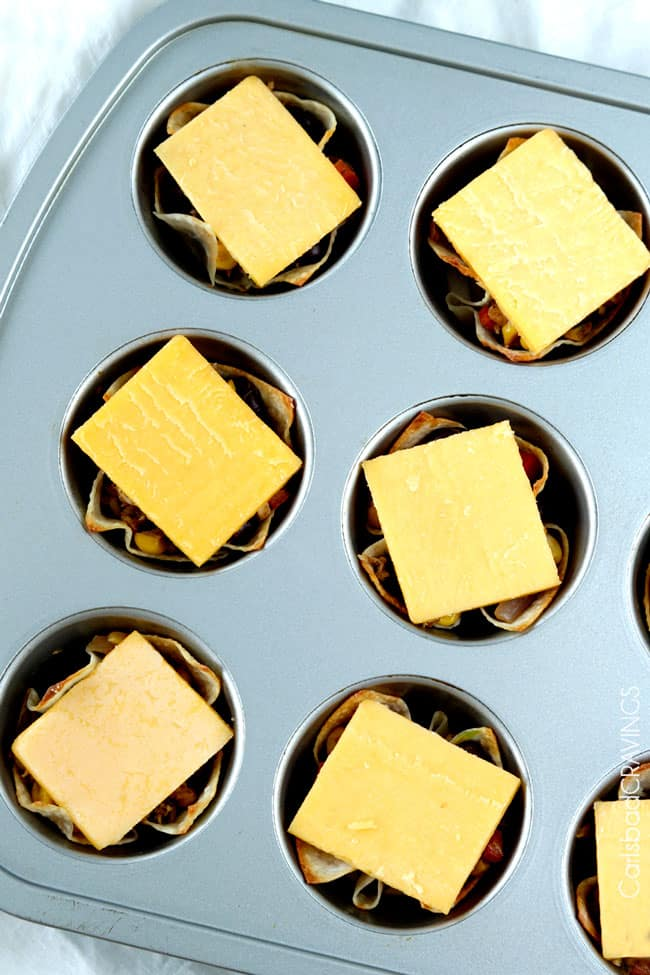 Tuna Melt Cups in muffin tin with cheese on top to be melted.
