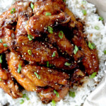 Baked General Tso's Sticky Wings over rice with green onion garnish.