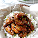 Baked General Tso's Sticky Wings over rice top view in a skillet.