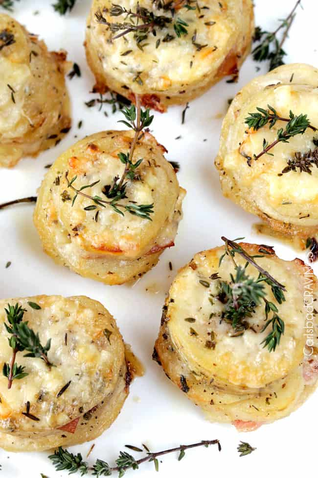 overhead view of cheesy potatoes and ham stacks topped with fresh thyme