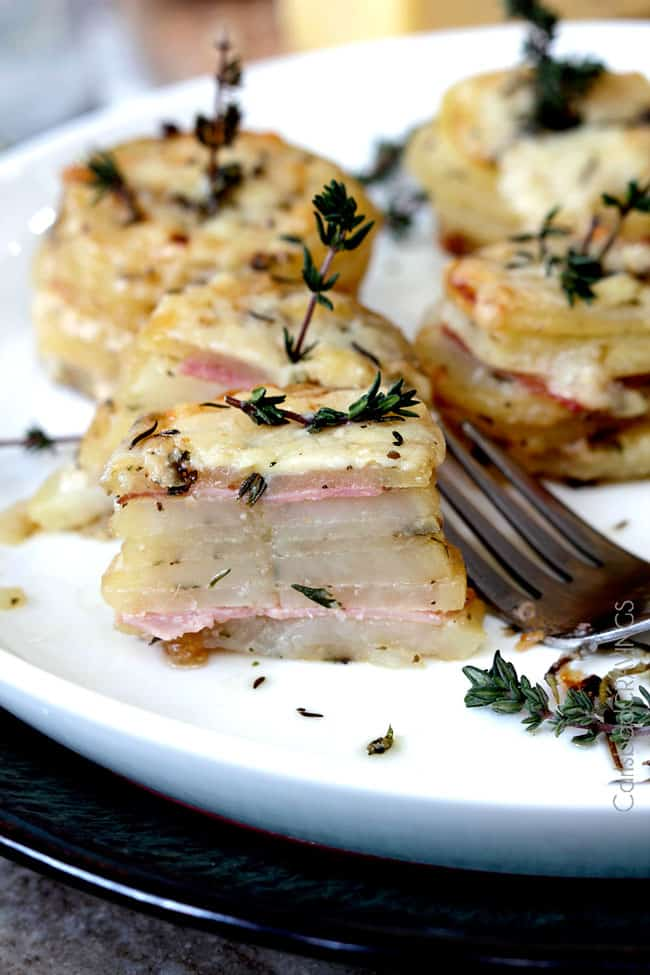 ham and potato stacks on a white plate. the front stack has been cut in half to show the layers.