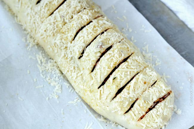 showing how to make stromboli by cutting slits into the top and placing in the oven to bake