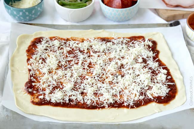showing how to make the Best Stromboli Recipe by adding mozzarella cheese on top of marinara sauce