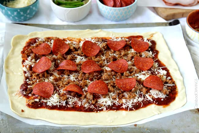 showing how to make Stromboli by topping cheese with pepperoni and Italian sausage