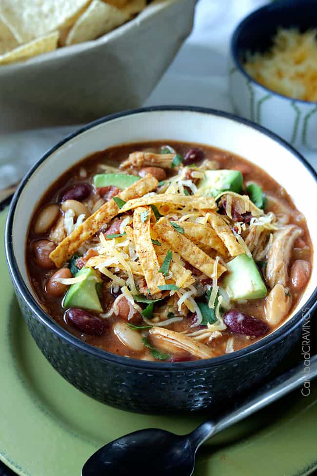 bowl of bbq chili garnished with tortilla strips and shredded cheese. A bowl of chips rests in the background
