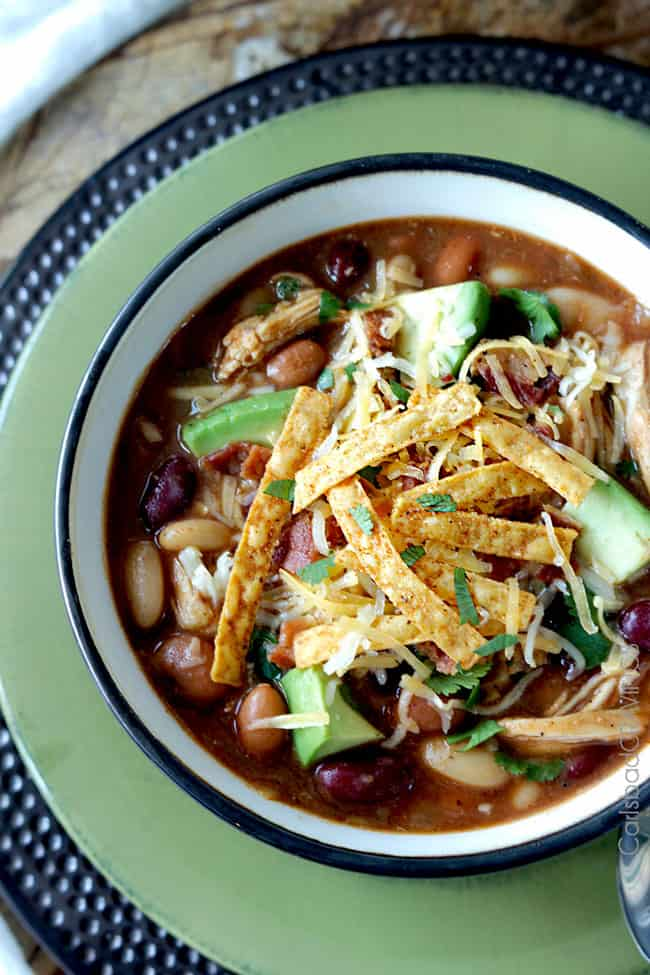 overhead view of bowl of bbq chicken chili garnished with tortilla strips and shredded cheese