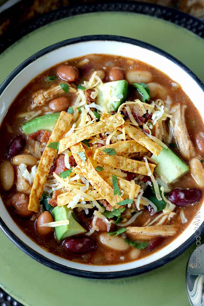 overhead view of bowl of chicken chili soup garnished with tortilla strips and shredded cheese