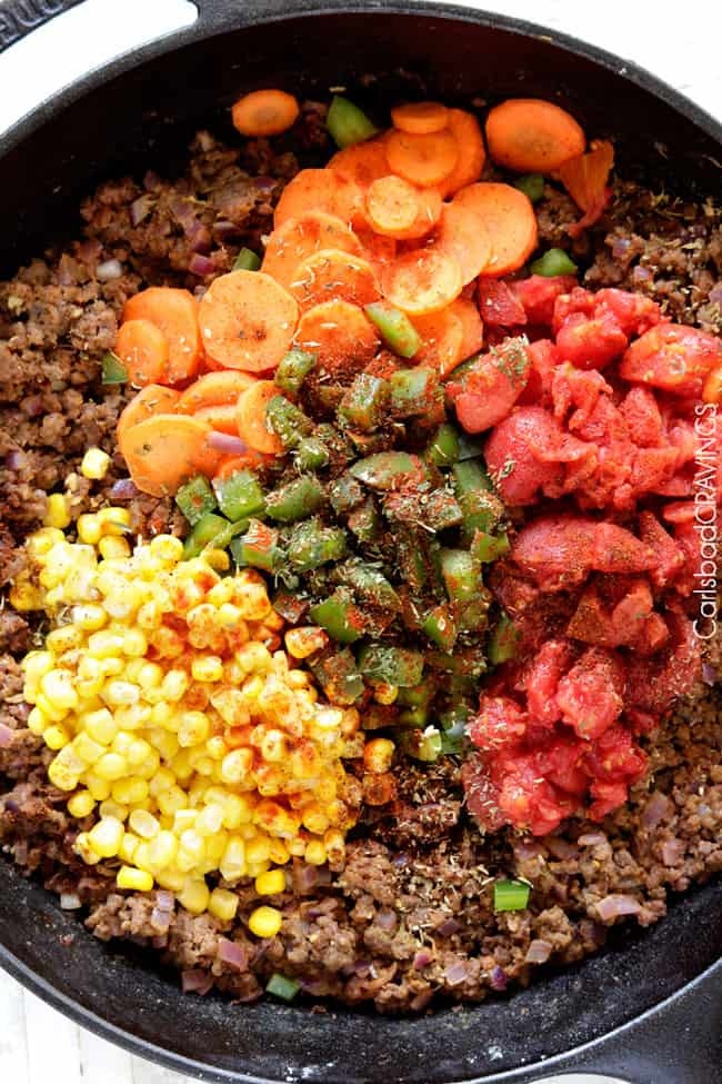 showing how to make shepherd's pie by adding carrots, corn, diced tomatoes, bell peppers and seasonings to ground beef
