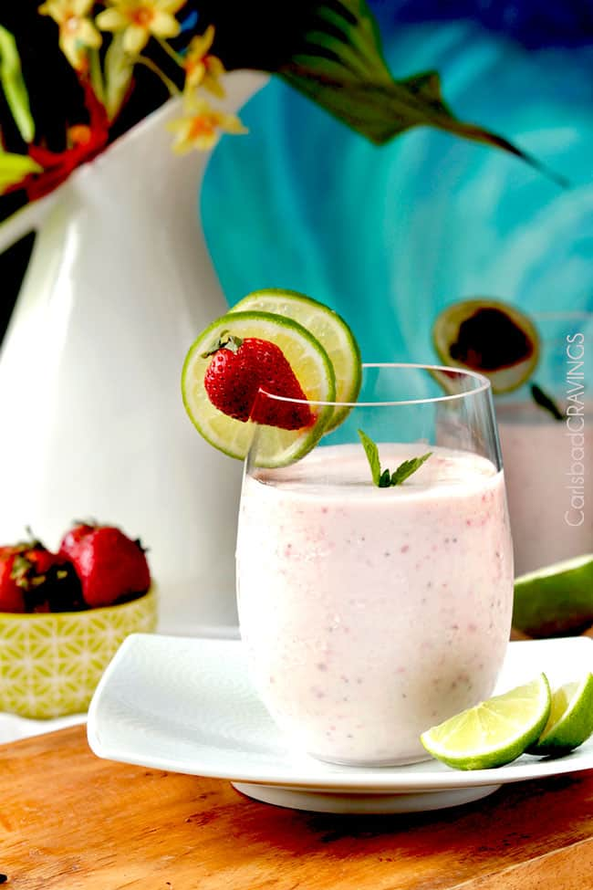 a glass of strawberry banana protein smoothie garnished with lime wedges and berries