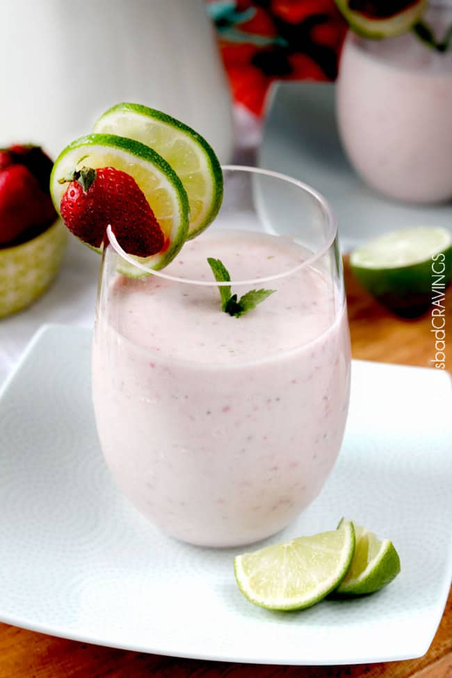 a strawberry banana protein powder smoothie in a glass on a white plate