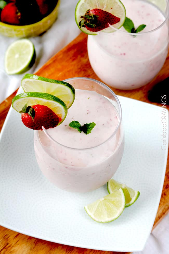 Top view of Strawberry Key Lime Banana Protein Smoothie in a glass with limes, strawberries and mint garnish.