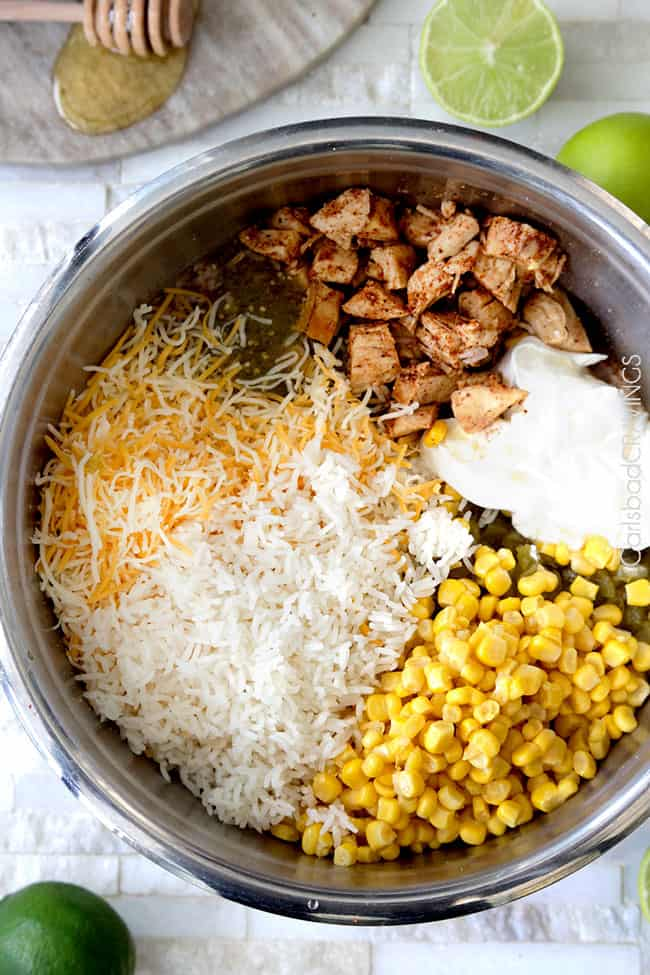 Showing how to make Salsa Verde Honey Lime Chicken by mixing cheese, corn, salsa verde, chicken in a bowl.