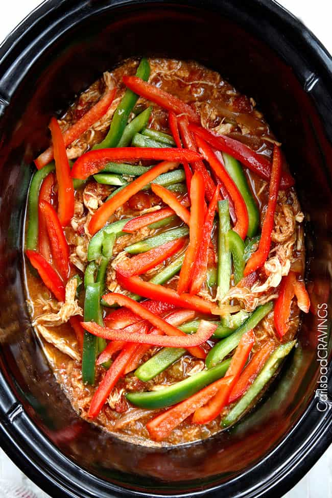 showing how to make easy crockpot chicken fajitas by adding bell peppers on top of shredded chicken in slow cooker