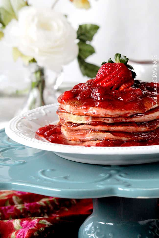 stack of strawberry pancakes on a white plate that's resting on a blue cake stand.
