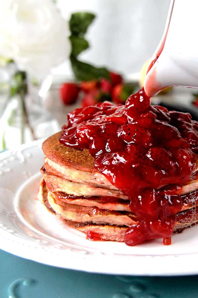 strawberry pancake syrup being poured over a stack of pancakes.
