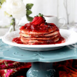 Side view of Top view of Strawberry Cheesecake Pancakes with strawberry syrup and strawberries garnished on top.