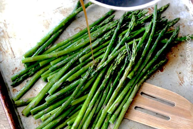 overhead view of showing how to make balsamic asparagus with asparagus on baking sheet with spatula