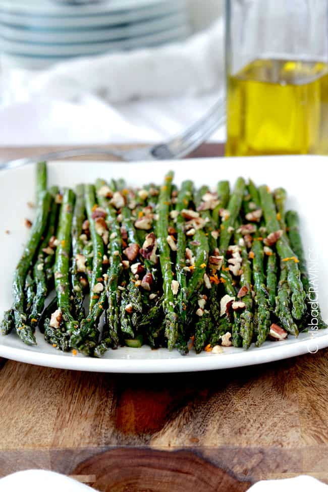 Front view of Fresh baked Roasted Asparagus on a white plate topped with nuts.