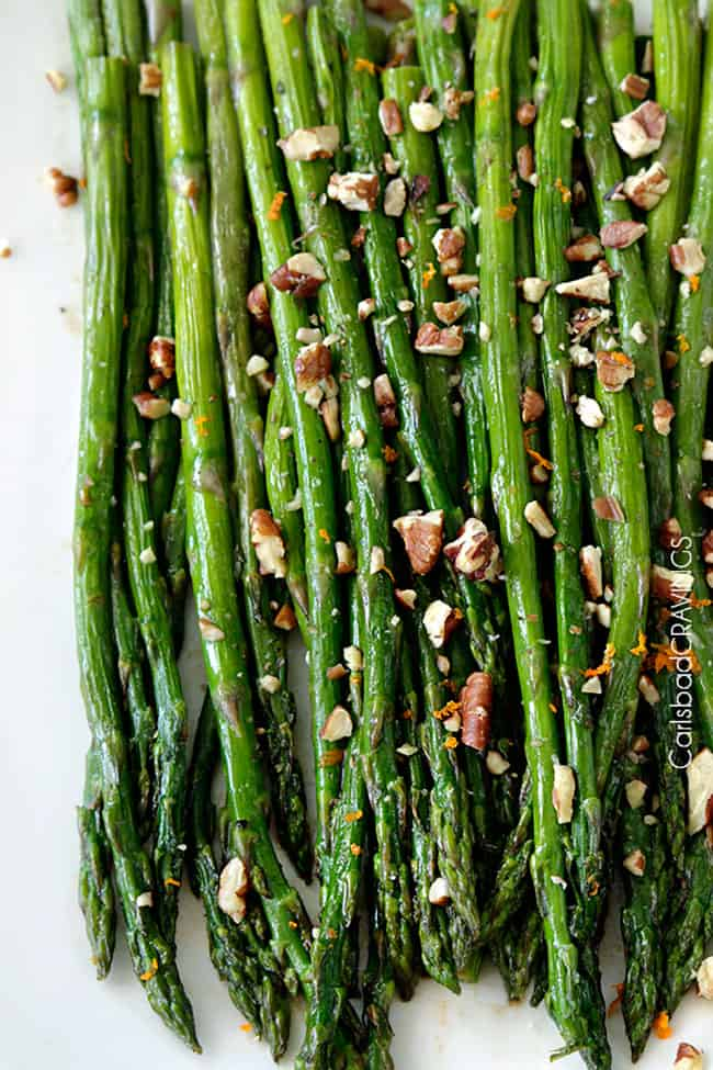 Close up top view of Fresh baked Roasted balsamic Asparagus on a white plate topped with nuts.