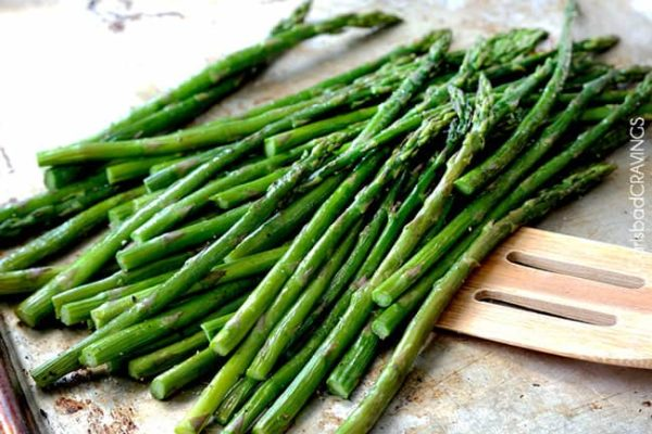 roasted asparagus on baking sheet being scooped up with a spatula