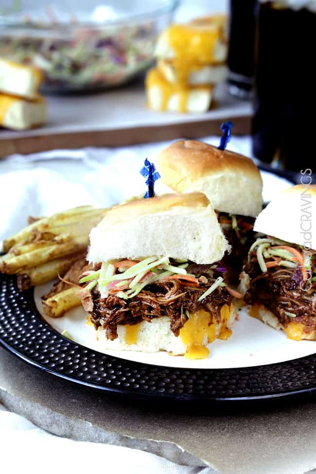 Three Cheesy BBQ Pork Sliders with Bacon Broccoli Slaw on a black and white plate with french fries.