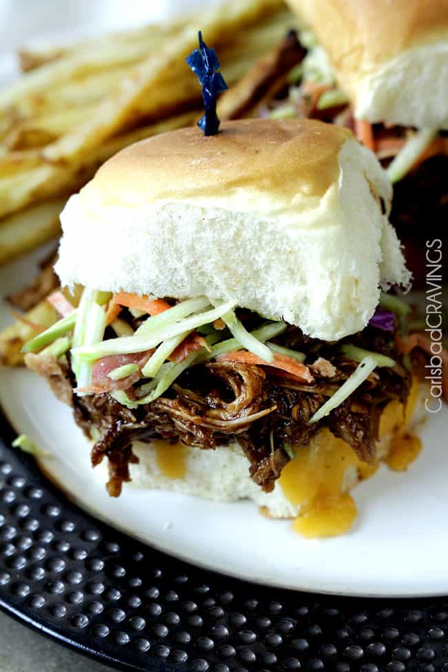 Very close up view of a Cheesy BBQ Pork Sliders with Bacon Broccoli Slaw on a black and white plate.