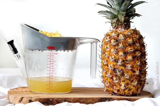 Showing how to make Coconut Rice with Pineapple and Cashews by straining the juice from a pineapple.