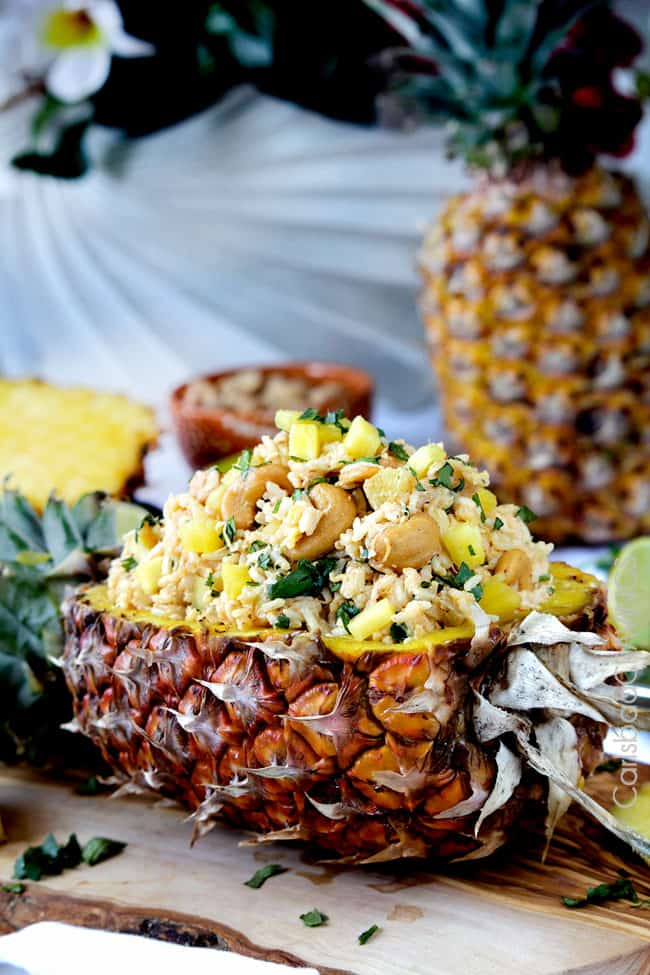 Side view of Coconut Rice with Pineapple and Cashews served in a pineapple with a heaping pile of rice.
