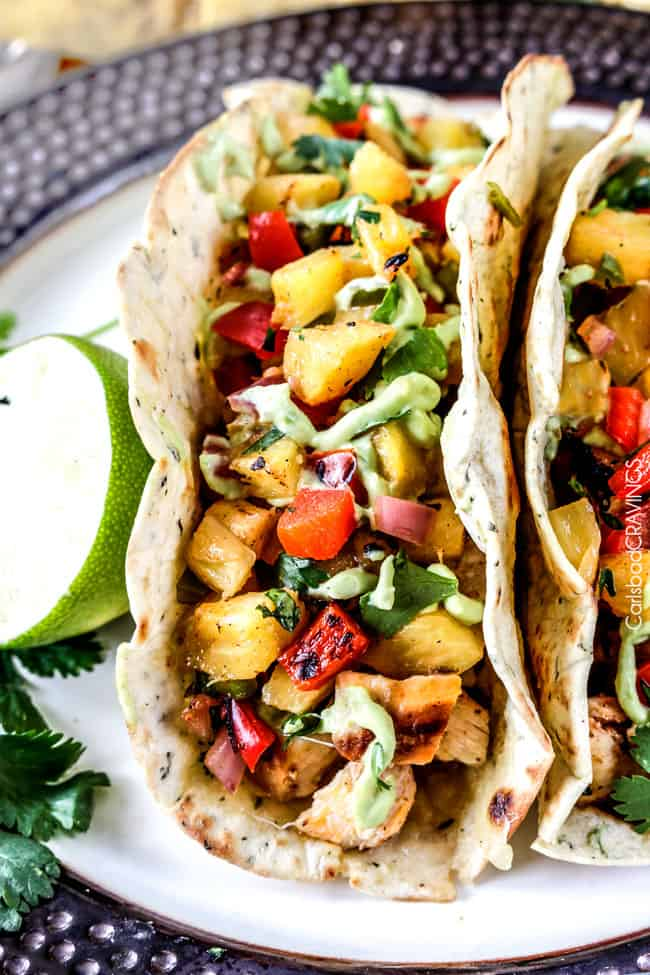 Close up of two Chili Lime Chicken Tacos with pine apple and lime.