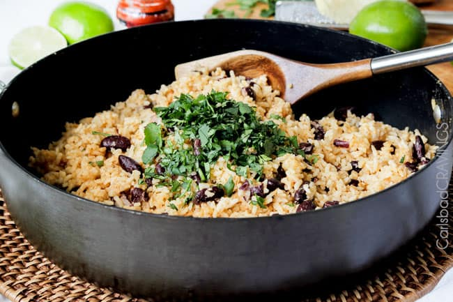 Showing how to make Red Beans and Rice by mixing rice and beans with cilantro.
