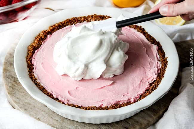 Showing how to make Frozen Lemon Meringue Pie by adding the white meringue on the top of the pink cake.