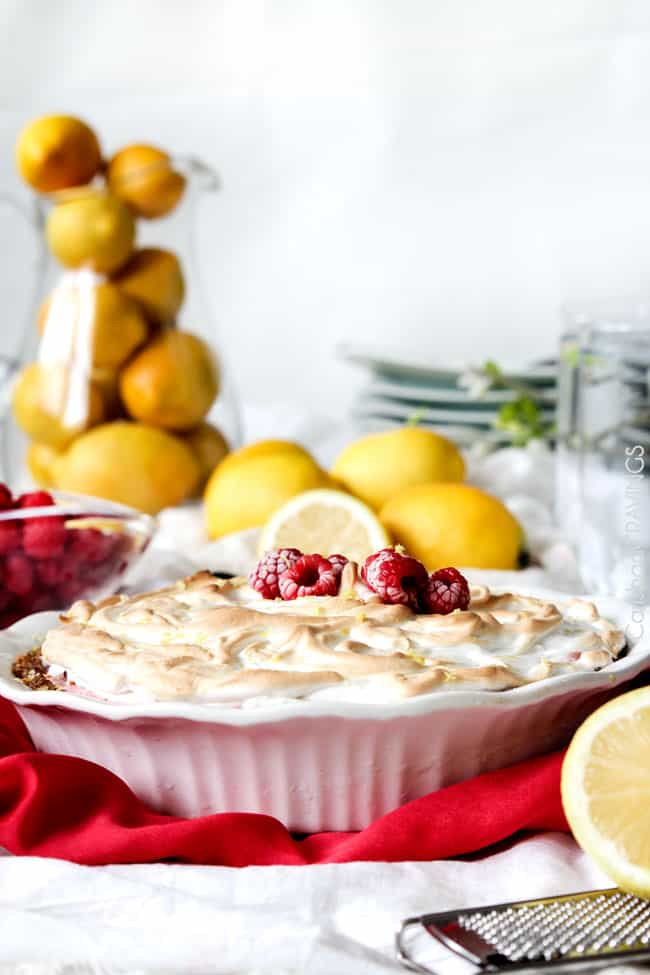 A full Frozen Lemon Meringue Pie in a white pie pan with raspberries and lemons on the side.