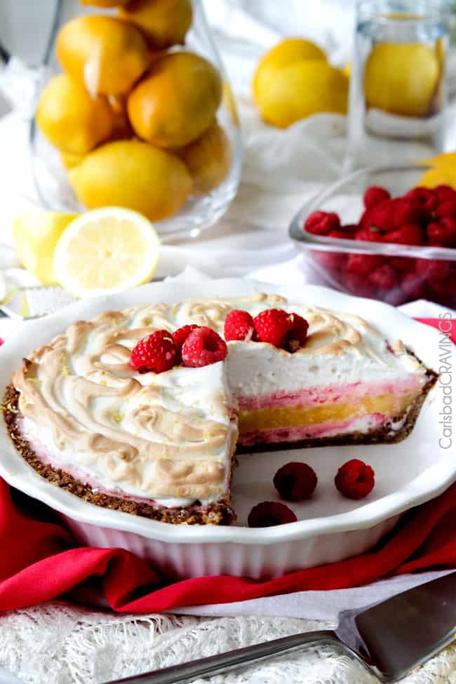 Frozen Lemon Meringue Pie on raspberries and a slice missing.