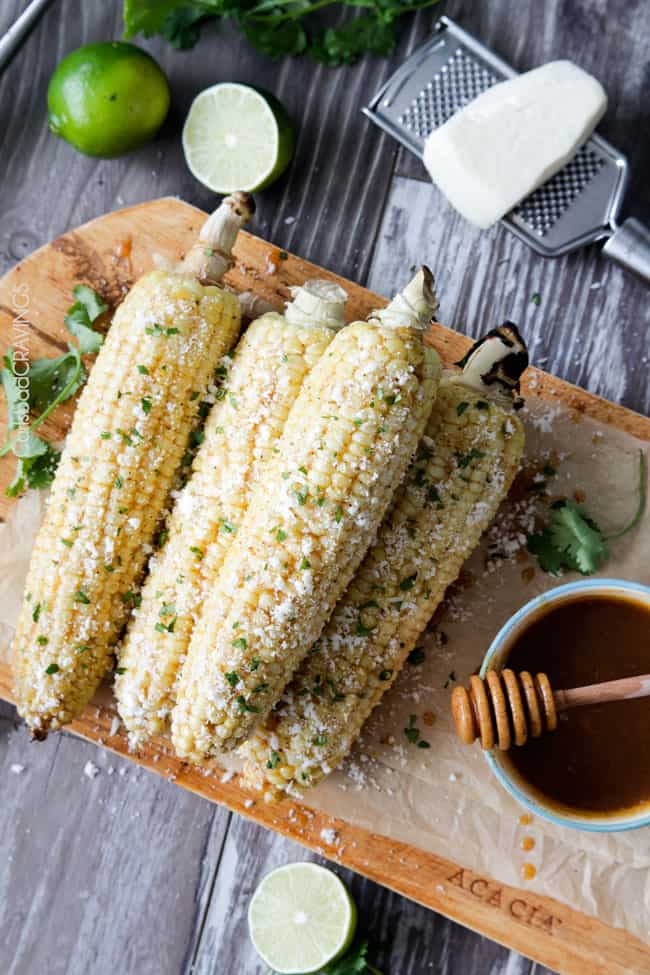 easy Roasted or grilled corn on the cob never tasted so amazing brushed with delectable Chipotle Honey Lime Butter sprinkled with cilantro and cotija cheese! Perfect for the 4th or roast year round. #corn #Mexicancorn #grilledcorn #chipotle