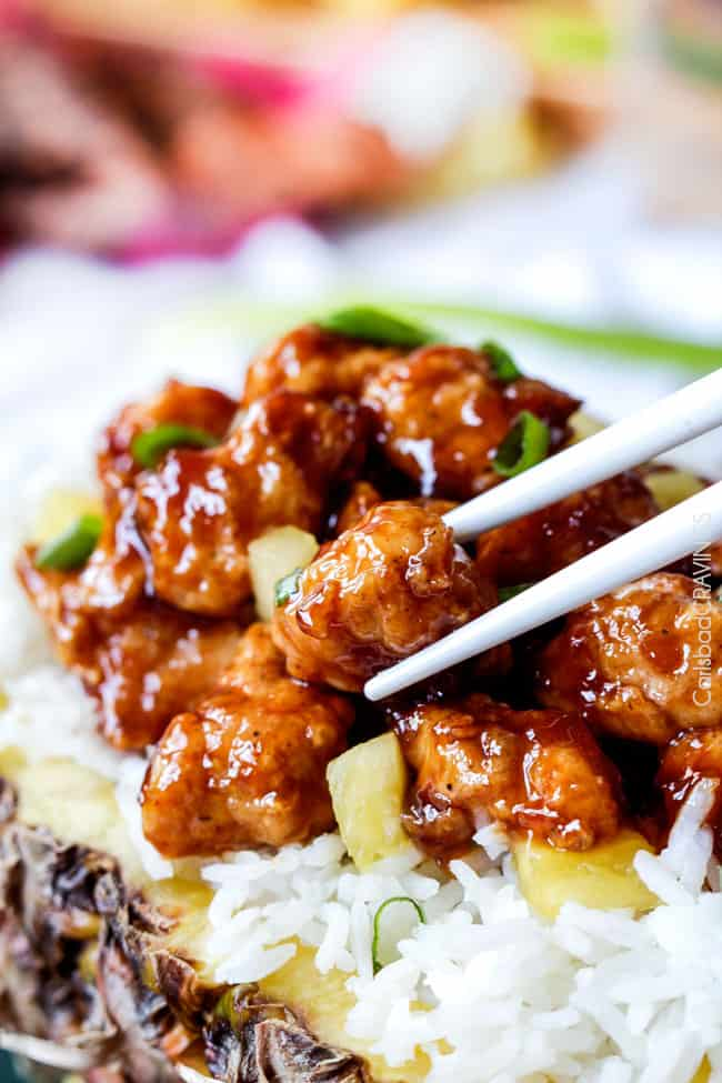 picking up Pineapple Ginger Chicken with chopsticks in a delicious pineapple sauce with white rice.