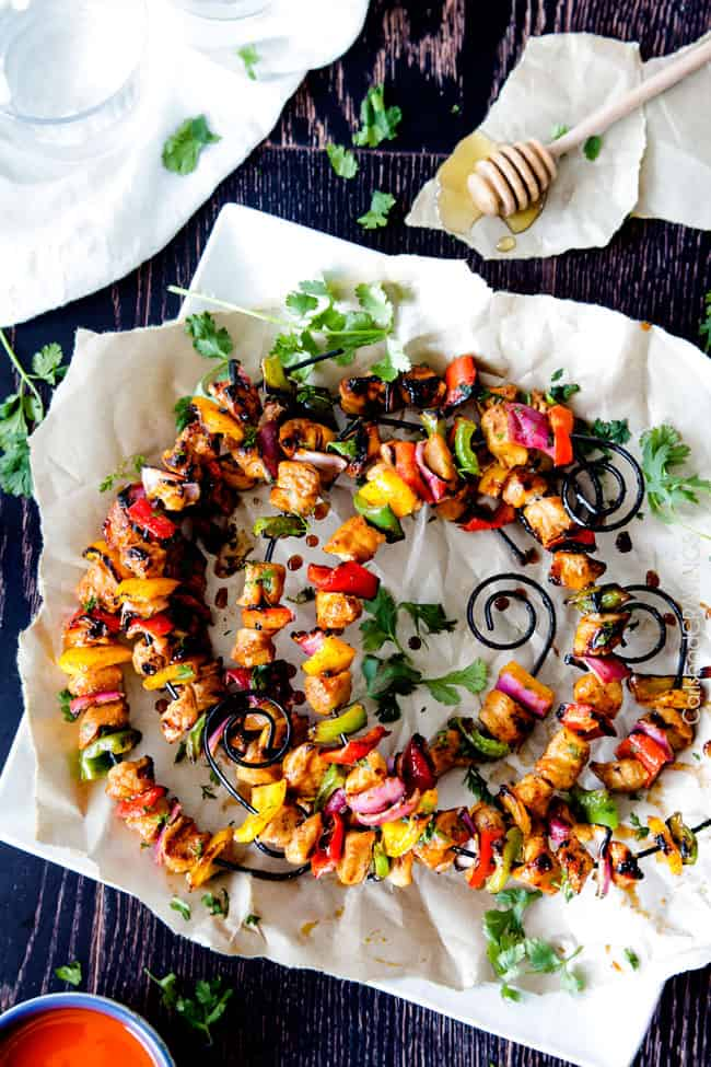 Honey Buffalo Chicken Fajita Kebabs on skewers on a white plate.