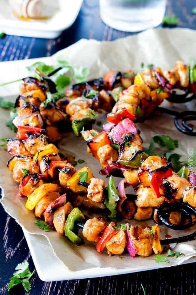 Honey Buffalo Chicken Fajita Kebabs on skewers with belle peppers and onions.