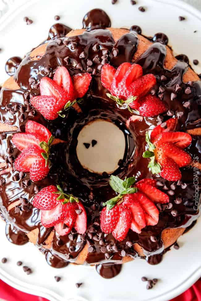 A delicious Strawberry Pound Cake covered in chocolate ganache on a white cake platter.