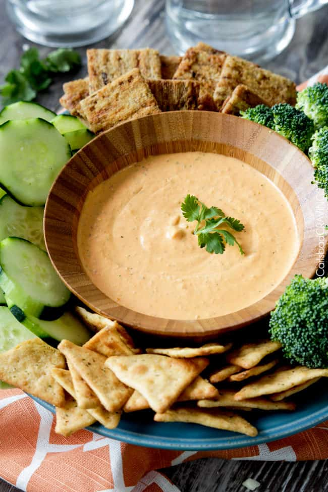 A a bowl of Roasted Red Pepper Feta Dip with vegetables and crackers around the bowl..