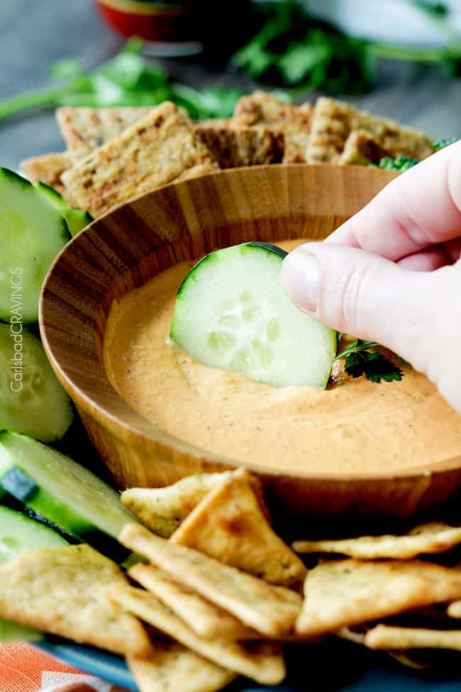 A cucumber being dipped in a bowl of Roasted Red Pepper Feta Dip.