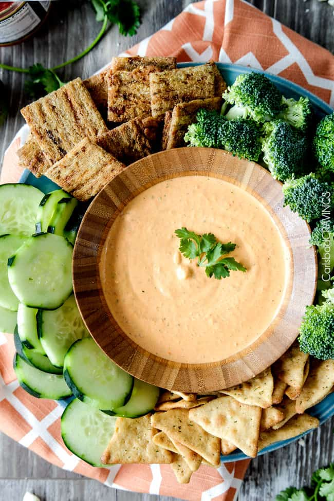 Top view of Broccoli and vegetables around a bowl of Roasted Red Pepper Feta Dip.