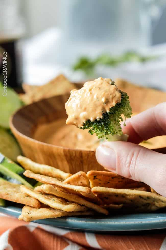 Broccoli held up with dip of Roasted Red Pepper Feta Dip.